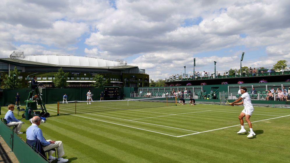Foto: Tomic, al fondo, durante el partido que le enfrentó a Tsonga en primera ronda de Wimbledon (Reuters/Toby Melville)