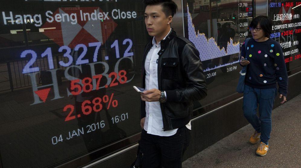 Foto: Peatones caminan junto a pantallas que muestran información bursátil en China. (EFE)