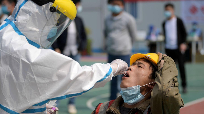 Un empleao sanitario le hace un test rápido de coronavirus a un trabajador chino en Wuhan. (Reuters)