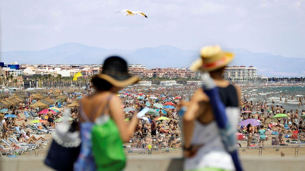 Foto: Una pareja observa las repletas playas de Las Arenas y La Malvarrosa, de Valencia. (EFE)
