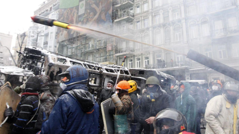 Manifestantes lanzan un proyectil pirotécnico contra la policía en Kiev (Reuters).