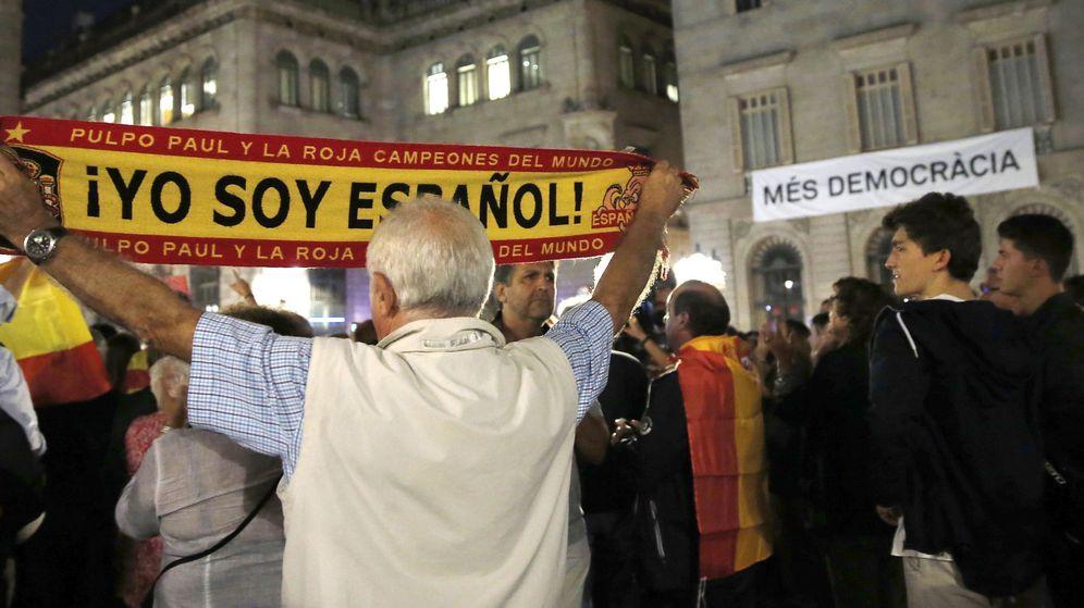 Foto: Un hombre sostiene una bandera con el lema 'Yo soy español' en Barcelona. (EFE)