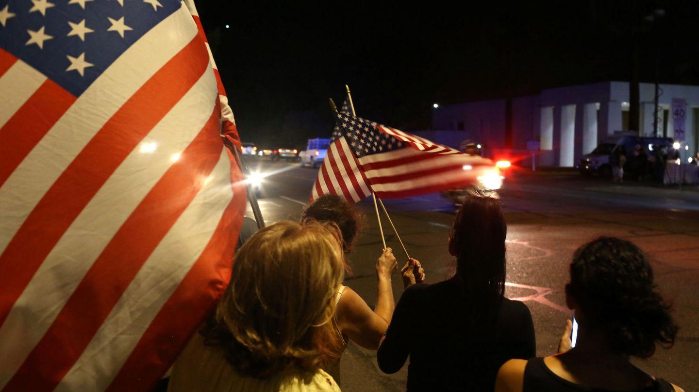 Decenas de personas han salido a la calle con banderas al paso del coche fúnebre con el cuerpo de McCain. (Reuters)