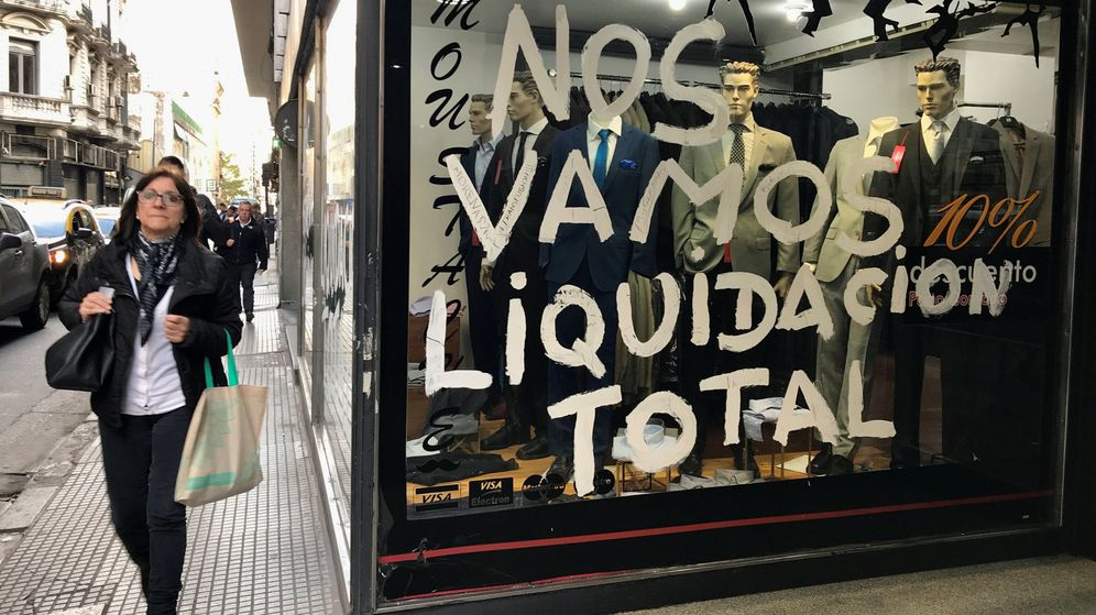 Foto: People walk by a store that is going out of business in buenos aires