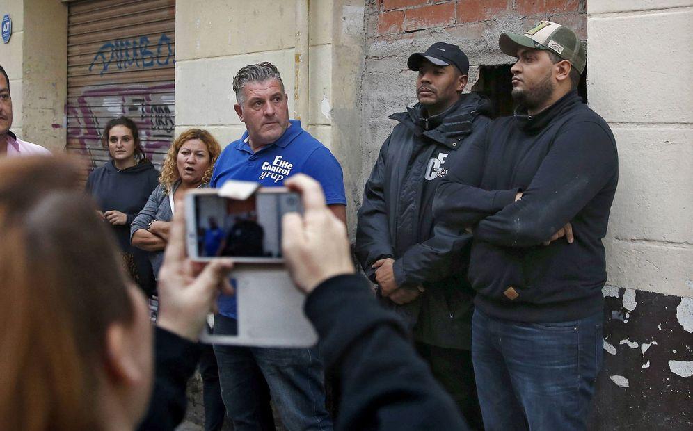Foto: Tres vigilantes custodian la entrada a un inmueble okupado en Barcelona. (EFE)