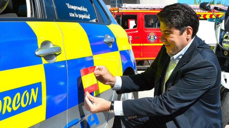 El alcalde de Alcorcón, colocando la bandera de España en un vehículo de la Policía Municipal.
