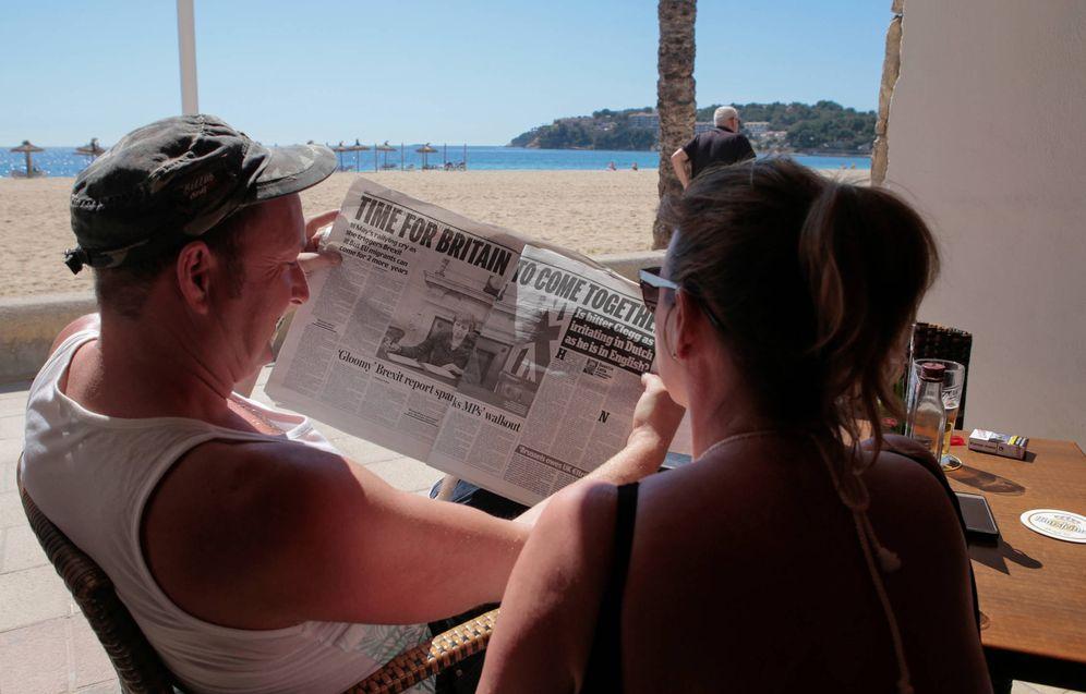 Foto: Dos turistas británicos leen un periódico en una terraza de Magaluf, Mallorca. (Reuters)