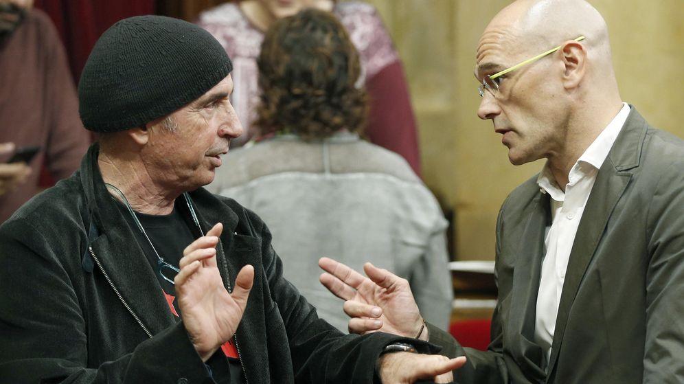 Foto: Los diputados de Junts pel Sí, Raül Romeva y Lluis Llach, este lunes en el hemiciclo del Parlament de Cataluña. (Efe)