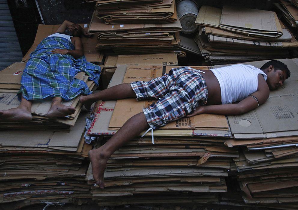 Foto: Trabajadores duermen sobre montaña de cartones en Mombai. (Reuters)