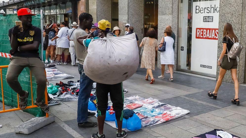 Foto: Un grupo de manteros muestra sus productos al público que transita por la Gran Vía de Madrid. (EFE)