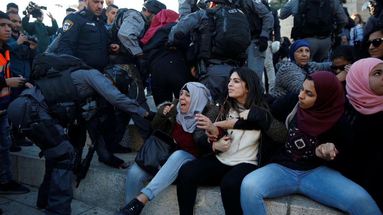 Un policía israelí en una refriega con una manifestante palestina en la Puerta de Damasco este viernes. (Reuters)
