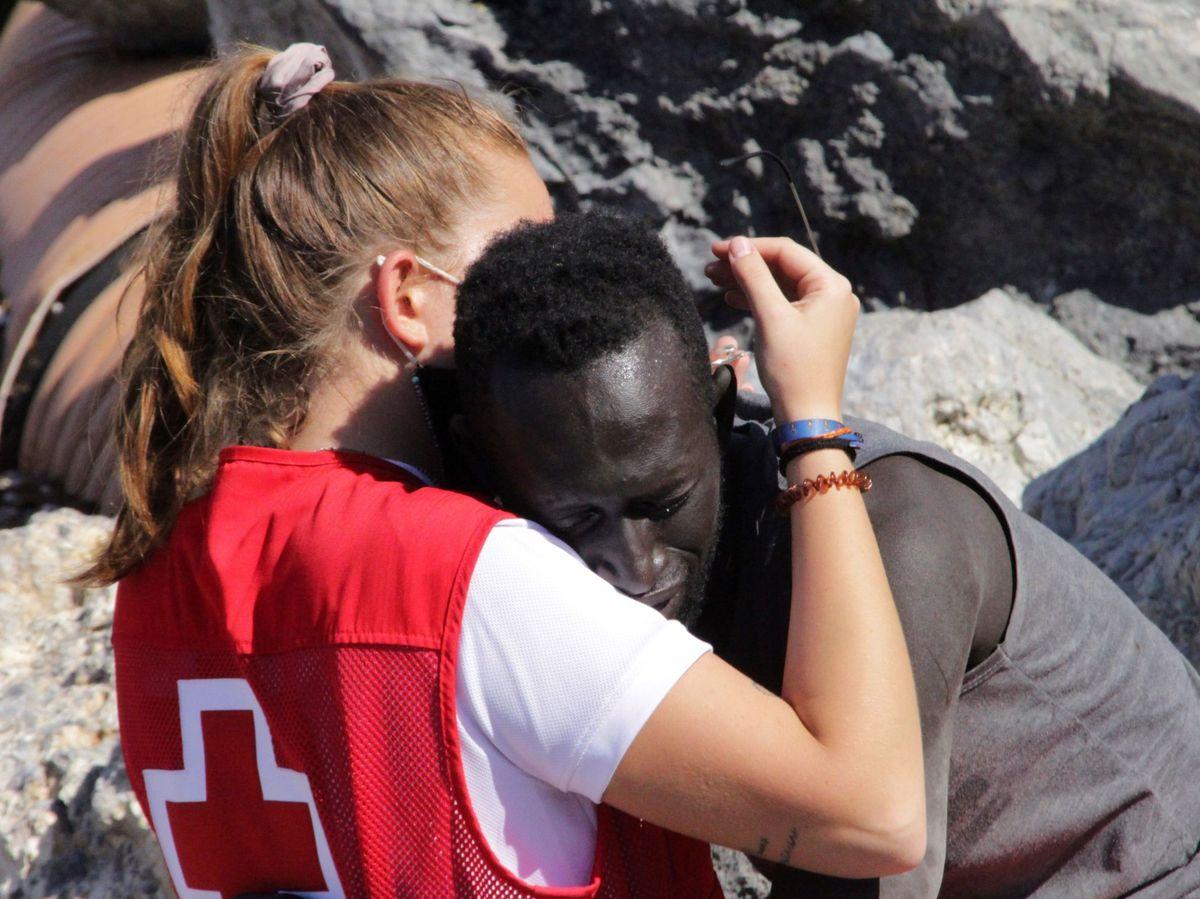 Foto: Luna consola a un migrante que ha logrado cruzar uno de los espigones fronterizos de Ceuta. (EFE)