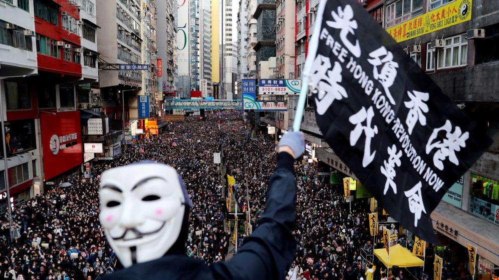 Foto: Un manifestante con una máscara ondea una bandera durante una marcha del Día de los Derechos Humanos. (Reuters)