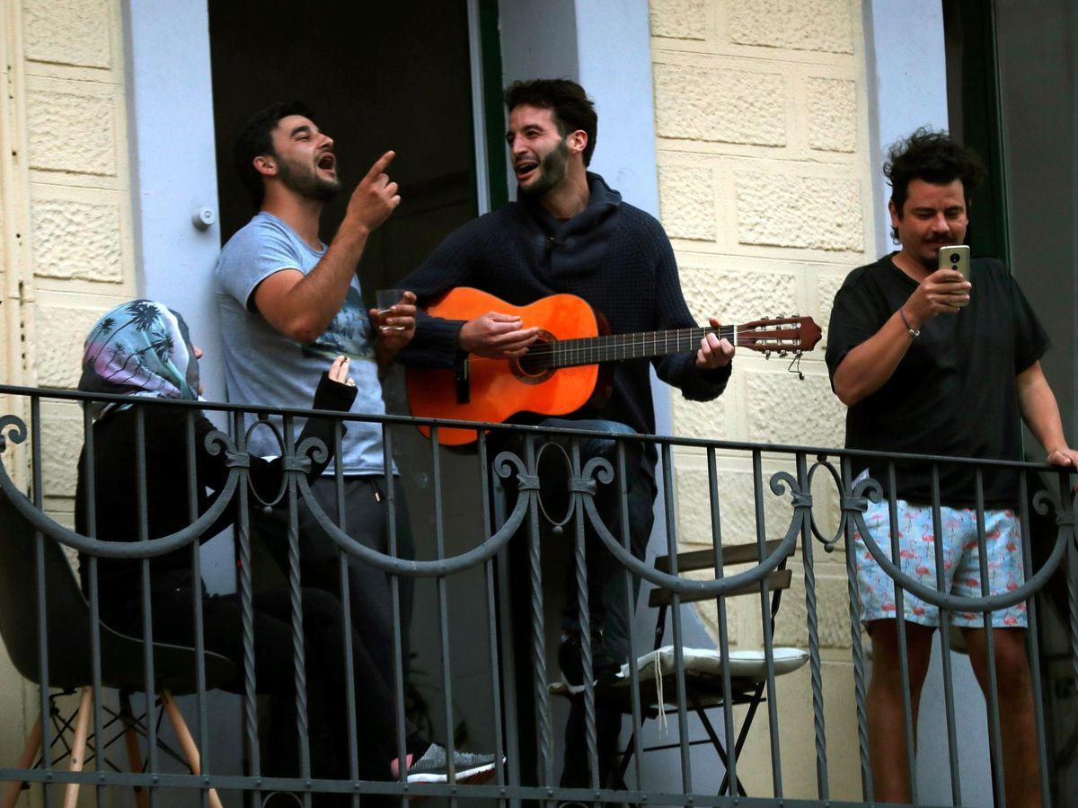 Foto: Vecinos de L'Hospitalet salen a sus balcones como cada día a animar y homenajear a los sanitarios. (EFE)