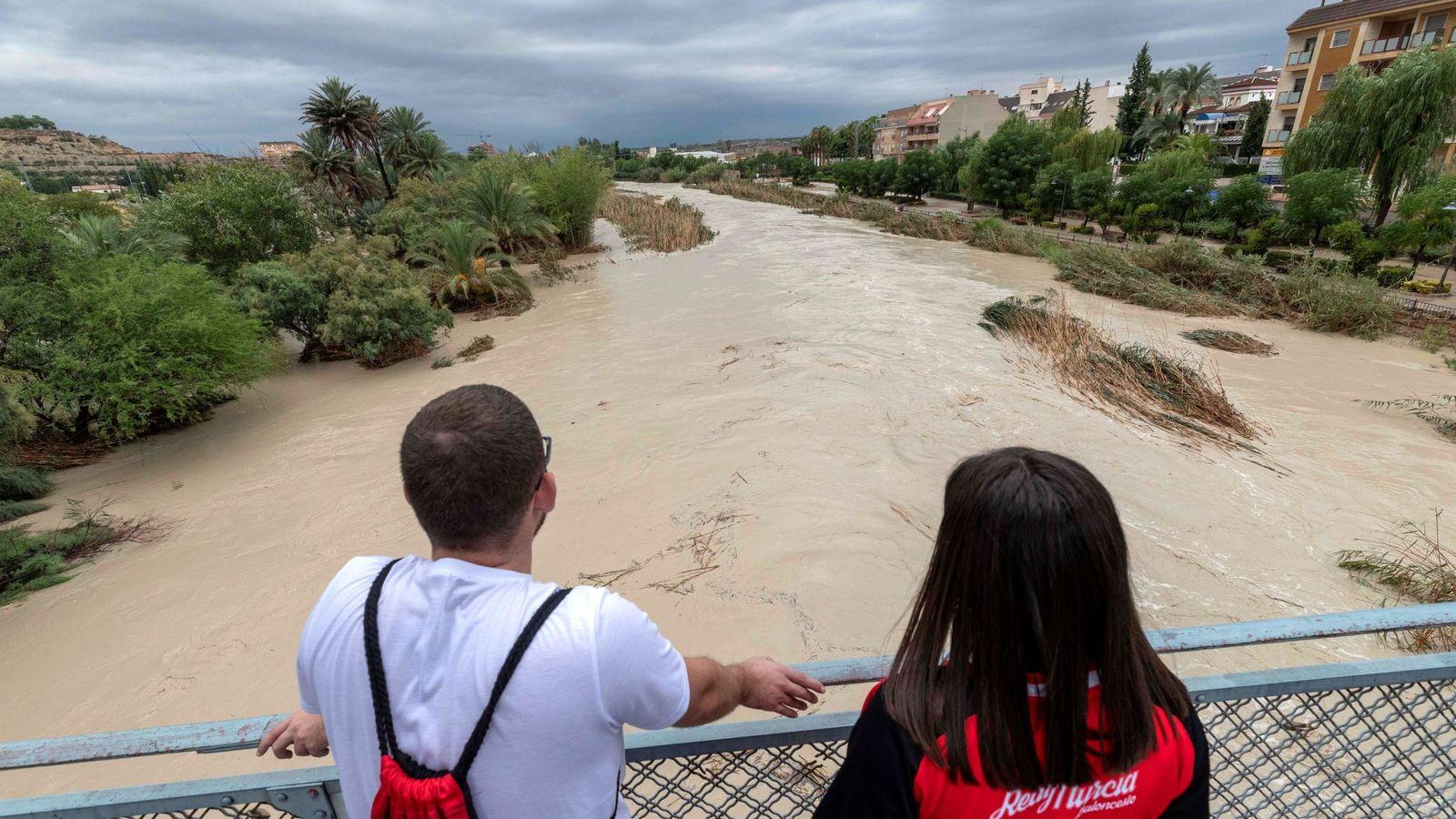 Foto: Dos chicos observan la crecida del río Segura tras desbordarse por las dos márgenes a su paso por Archena, Murcia. (EFE)