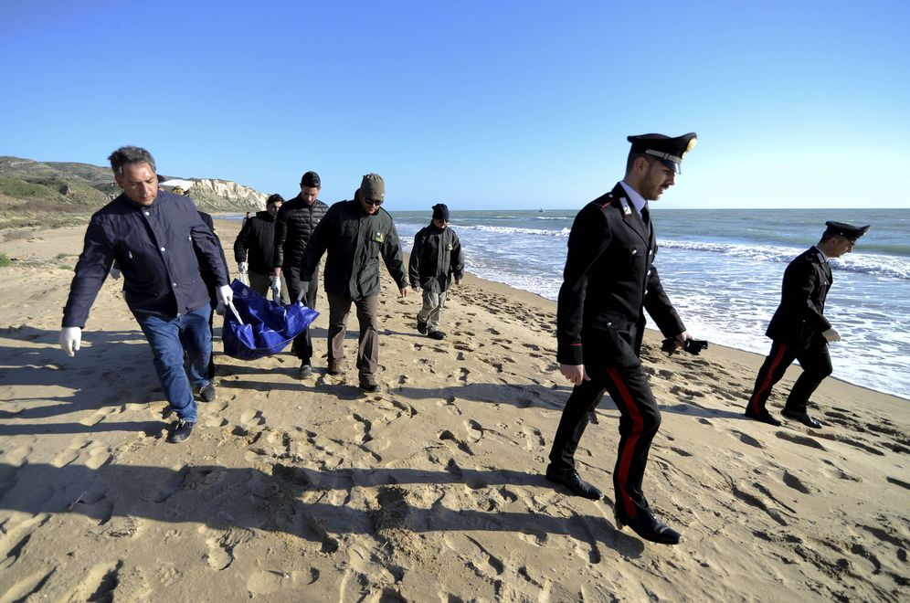 Foto: Agentes transportan el cadáver de un inmigrante en la playa de Siculiana, Sicilia. (Reuters)