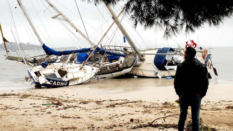 Un hombre mira tres de las embarcaciones varadas en la arena en el Port de Pollença (Mallorca) (EFE)