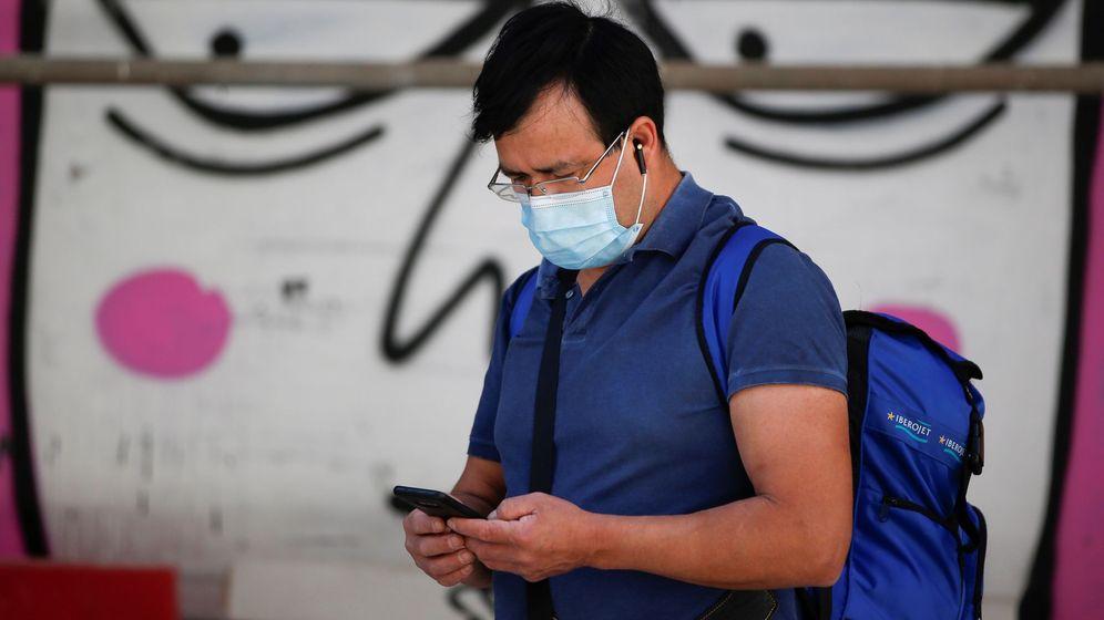 Foto: Un ciudadano revisa su teléfono en el centro de Madrid. (EFE)
