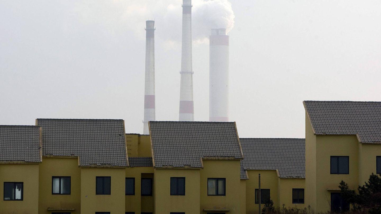 Tres chimeneas humeantes asoman tras un conjunto de viviendas deshabitadas en la ciudad de Qingdao, en la provincia china de Shandong. (EFE)