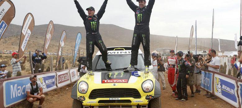 Foto: Nani Roma y su copiloto Michel Perin celebran su primer triunfo en la categoría de coches (Efe).