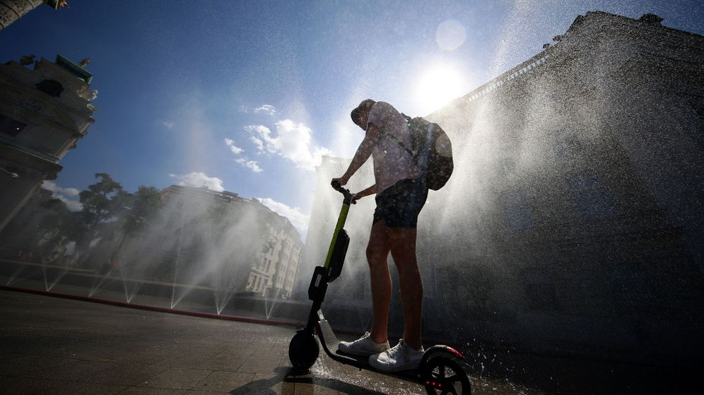 Foto: A man rides an electric scooter under water sprinklers during a heat wave in vienna