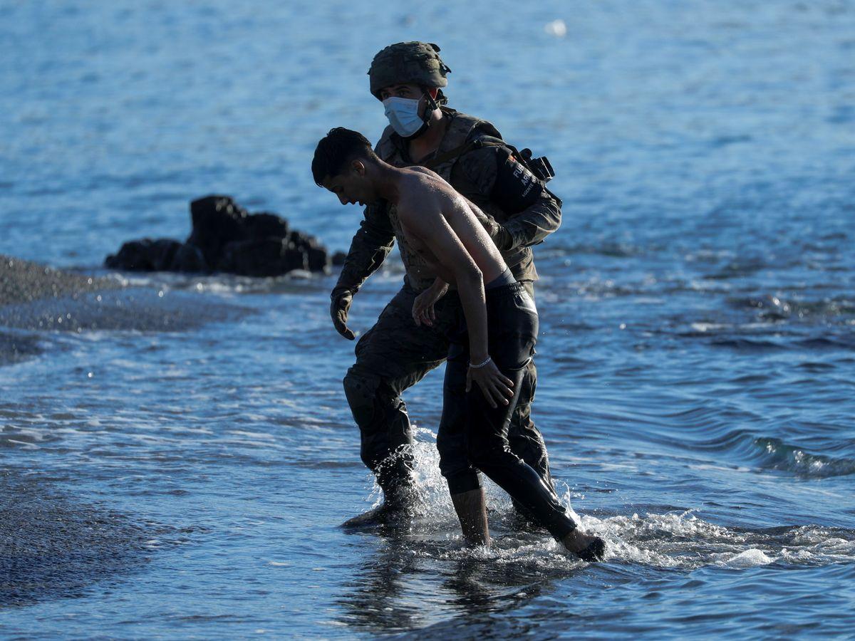 Foto: Un militar ayuda a salir del agua a un inmigrante en Ceuta. (Reuters)