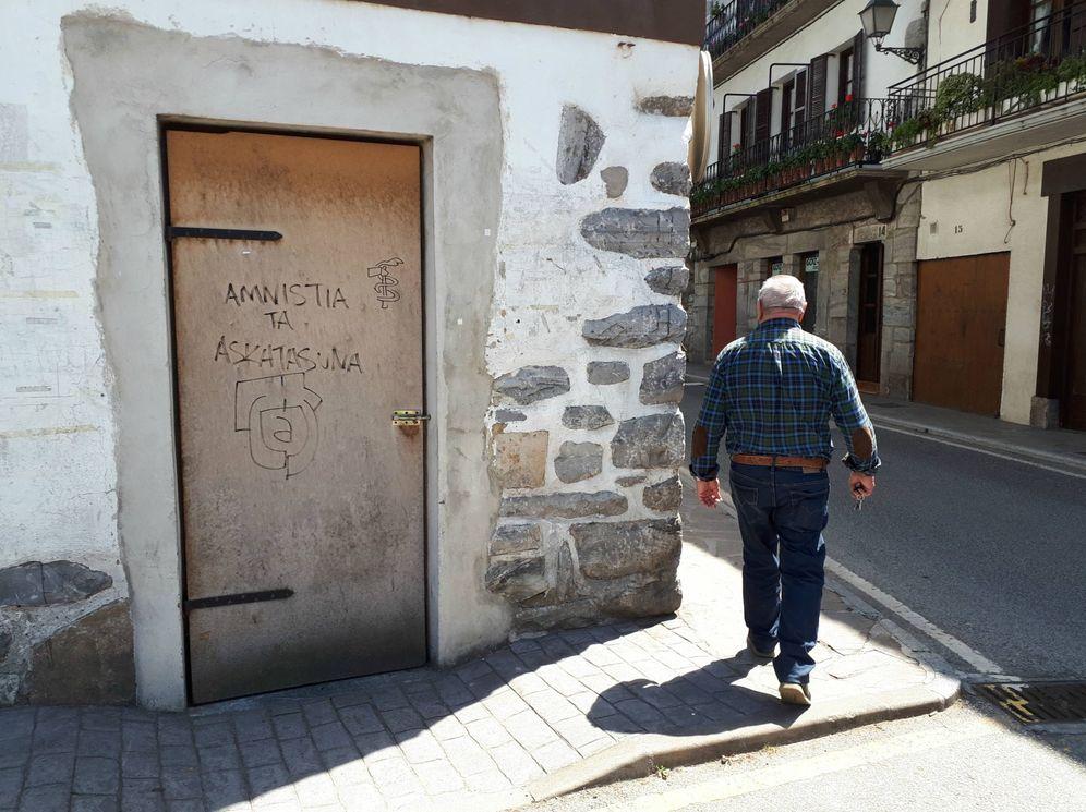 Foto: Un hombre pasa por delante de una puerta con una pintada con el símbolo de ETA que pide amnistía y libertad en Lesaka. (J. M. A.)