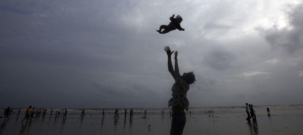 Foto: Un padre juega con su bebé durante el monzón en una playa de Mumbai (Reuters).