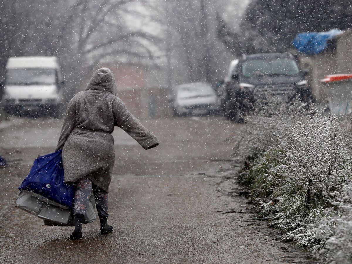 Foto: Una vecina del asentamiento de la Cañada Real camina bajo la nieve, este jueves. (EFE)