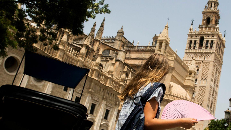 Una mujer pasa ante la catedral de Sevilla. (EFE)