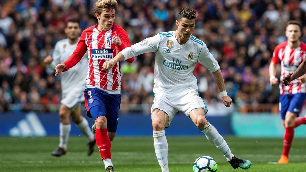 Foto: Cristiano Ronaldo protege un balón en presencia de Griezmann. (EFE).