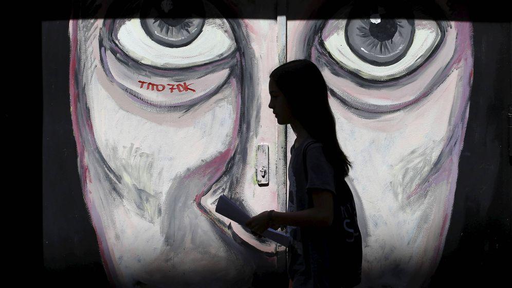 Foto: Una mujer pasa por delante de un grafiti en el barrio de Malasaña, en Madrid. (Reuters)
