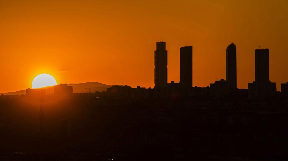 Foto: Puesta de sol tras las emblemáticas Cuatro Torres del Paseo de la Castellana. (EFE)