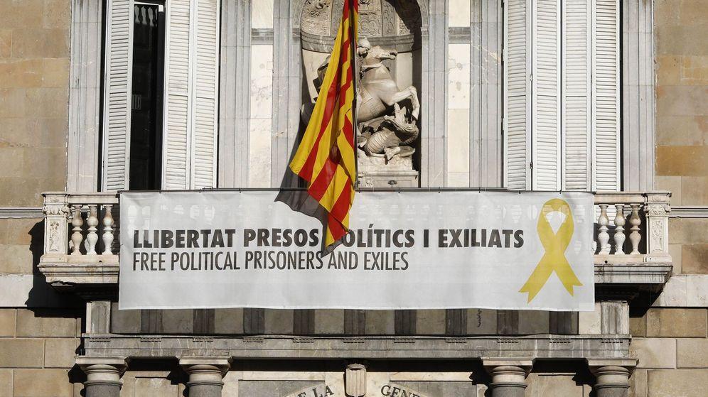 Foto: El cartel reclamando la libertad de los líderes independentistas presos y un lazo amarillo en la fachada del Palau de la Generalitat. (EFE)