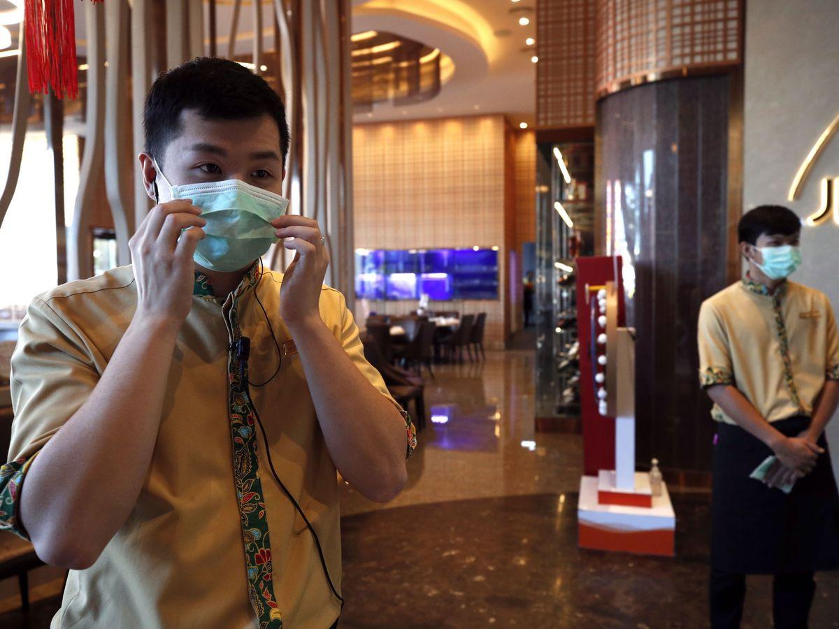 Foto: Dos camareros con mascarilla para evitar el contagio del coronavirus, en Tailandia. (Reuters)
