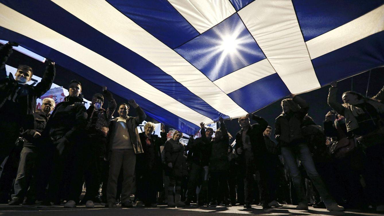 Foto: Manifestante sostienen una bandera griega durante una protesta contra la troika en Atenas, el 15 de febrero (Reuters).