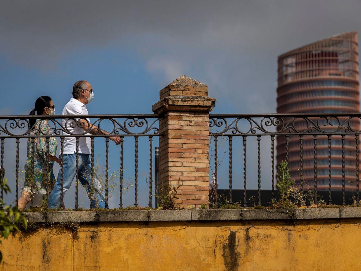 Foto: Dos personas con mascarillas cruzan el Puente de Triana, con la Torre Sevilla de fondo. (EFE)
