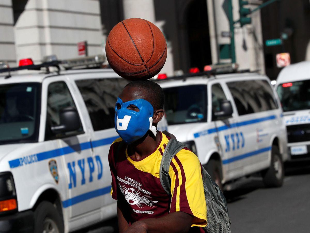 Foto: Un manifestante en Nueva York pasa junto a unos coches de la policía. (Reuters)