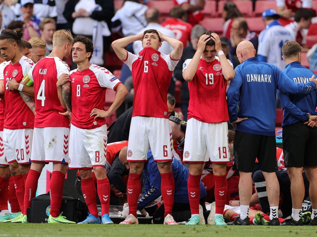 Foto: Los jugadores daneses protegen la intimidad de su capitán mientras era reanimado. (EFE)