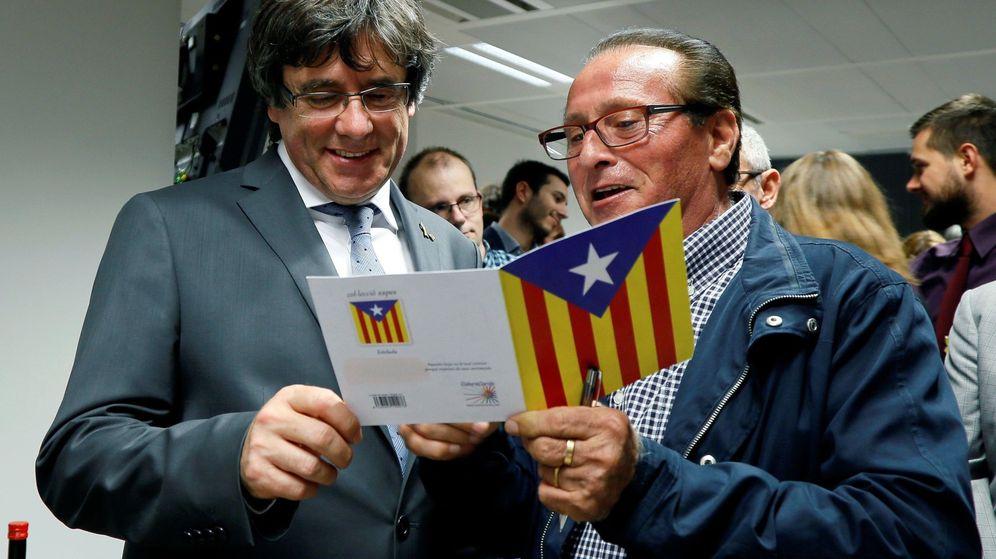 Foto: El expresidente de la Generalitat Carles Puigdemont (i) firma una tarjeta a un simpatizante durante el acto de celebración de la Diada en Bruselas. (EFE)