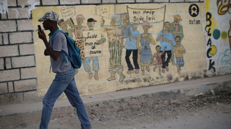 Un joven pasa frente a un cartel de Oxfam en Corail, en las afueras de Puerto Príncipe. (Reuters)