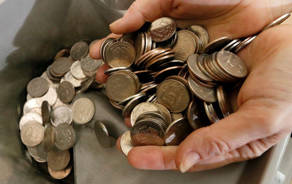 Foto: Foto de archivo de un hombre con monedas rusas en la mano. (Reuters)