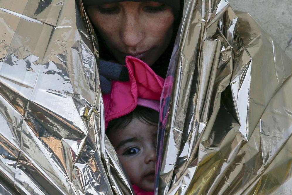 Foto: Una refugiada y su hija, envueltas en una manta térmica mientras esperan un tren a Croacia en la estación de Presevo, Serbia, el 20 de enero de 2016. (Reuters)