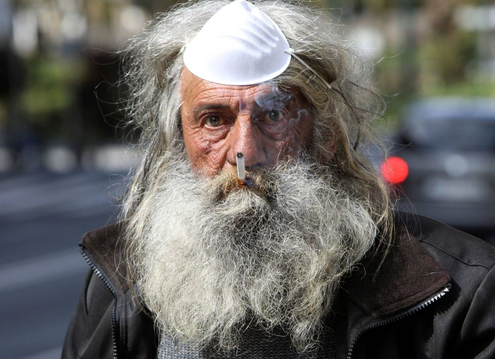 Foto: Un vecino espera el autobús para dirigirse a su casa. (Xoán Rey/EFE)