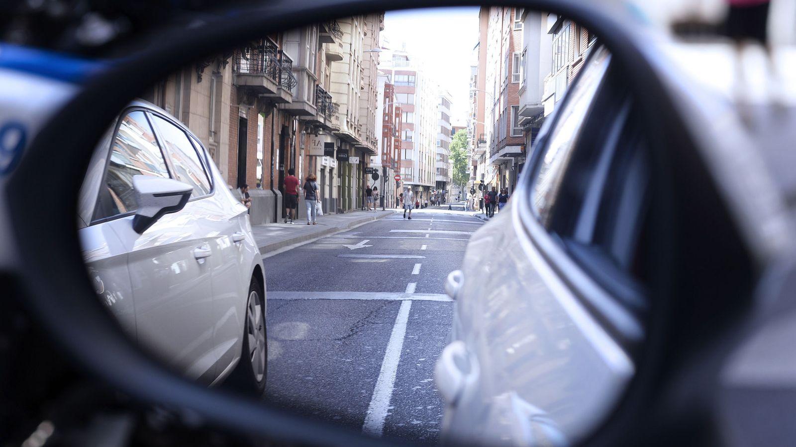 Foto: Un peatón se refleja en el retrovisor de un coche. (EFE)