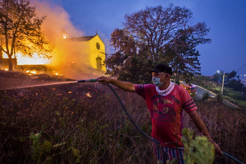 Foto: Un residente utiliza una manguera de jardín para ayudar en la extinción de un incendio en Funchal, isla de Madeira, el 10 de agosto (Reuters).