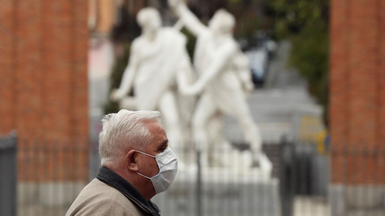 Foto: Un hombre protegido con una mascarilla transita una calle del madrileño barrio de Malasaña (EFE)