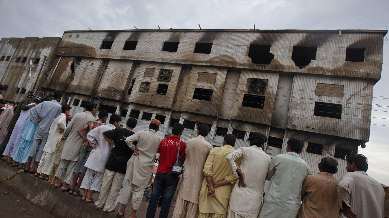 Un grupo de hombres observa la fábrica quemada, dos días después del incendio. (Reuters)