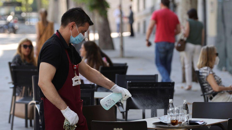 Foto: Un camarero desinfecta una mesa en una terraza de Madrid. (Efe)