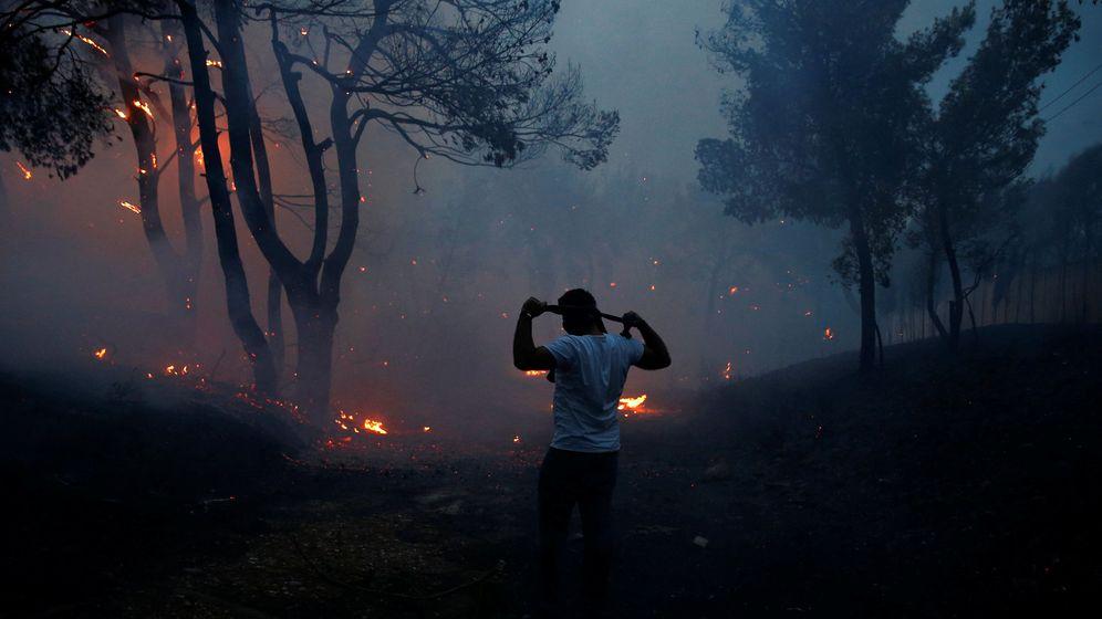 Foto: Un hombre usa ropa para protegerse del humo en Rafina, Grecia. (Costas Baltas / Reuters)